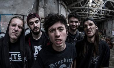 Retrat dels membres de la banda en una antiga nau industrial abandonada i fent ganyotes a la càmera