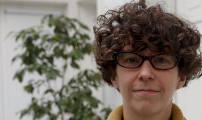 Retrat de la dramaturga Manuela Infante autora del muntatge Estado vegetal amb el cabell arrissat, ulleres de pasta i una planta al fons