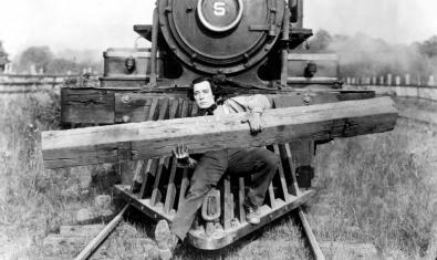 Fotograma de la pel·lícula, Buster Keaton a la part del davant del tren aguantant una via de fusta