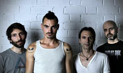 Retrato de plano medio de los integrantes de la banda con una pared blanca de fondo