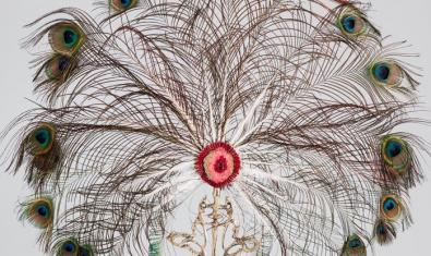 Una de les obres de l'exposició recorda un reliquiari religiós fet amb plomes de gall d'indi i amb la imatge d'un sexe femení al centre