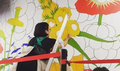 La artista subida a una escalera y pintando su obra mural