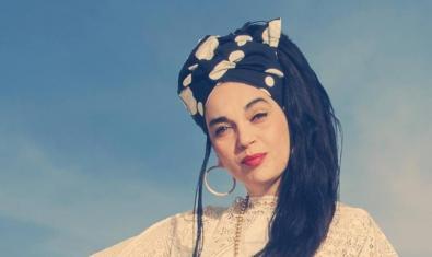 La que fuera vocalista de la banda Ojos de Brujo retratada bajo un cielo azul con un turbante en la cabeza