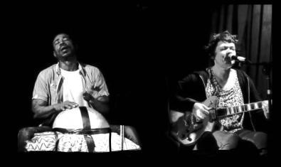 Retrato de ambos músicos tocando juntos ella con la guitarra en las manos y él haciendo percusión sobre una gran calabaza