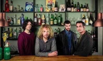 Los cuatro miembros de la banda detrás de una barra de bar rodeados de botellas