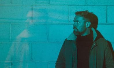 El artista de folk rock retratado bajo una luz azulada contra una pared de ladrillos