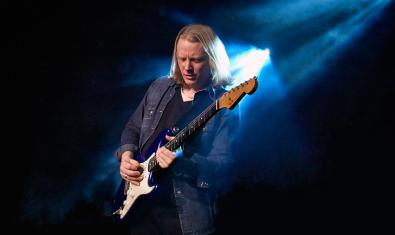 El artista tocando la guitarra iluminado por un foco en un escenario