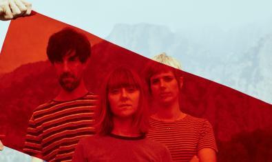 Les integrants de la formació retratades amb un paisatge de muntanya al fons i amb un filtre de color vermell al davant
