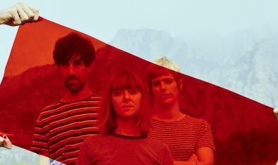 Els tres membres de la banda retratats en plena natura darrere d'una planxa transparent de color vermell