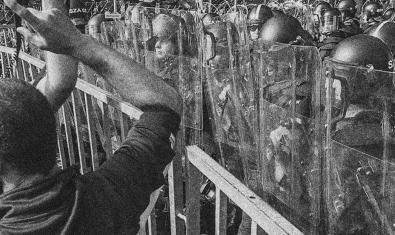 Un manifestant retratat per Felipe Abreu davant d'un escamot de policia antidisturbis