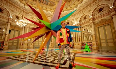 L'artista retratat davant de la instal·lació del Saló Miralls amb una mena de gran rosa dels vents tridimensional a l'esquena