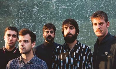 Els cinc membres de la banda retratats contra un fons que recorda una imatge de l'univers