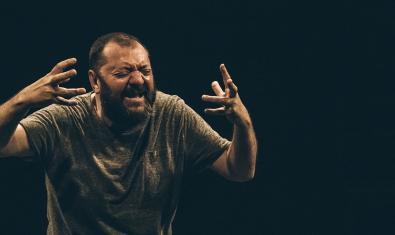 Un dels actors de la companyia retratat gesticulant amb les mans durant l'actuació