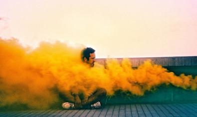 L'artista assegut al terra i envoltat d'un fum de color taronja