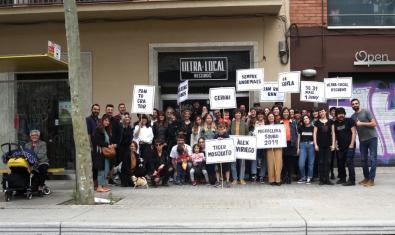 Un grup de prop de quaranta persones davant la seu d'Ultra-Local Records amb cartells que anuncien els grups participants al Microclima Sound d'enguany