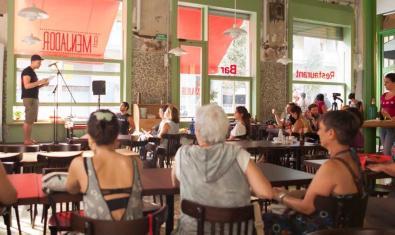 Una edició anterior d'aquesta activitat amb el bar de la Sala Beckett ple de gent escoltant un autor davant d'un micro