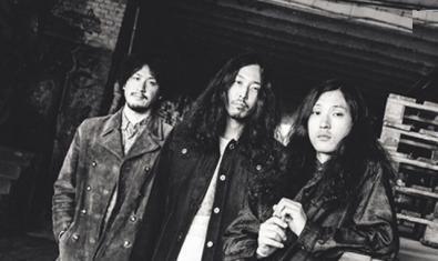 Els tres membres de la banda amb els cabells llargs retratats en blanc i negre en un magatzem