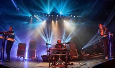 Els membres de la formació, retratats durant una actuació amb l'escenari il·luminat per una llum de color blau