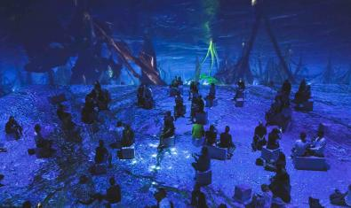 Un grupo de espectadores sentados a oscuras en una estancia en la cual las imágenes se proyectan en las paredes creando un efecto inmersivo