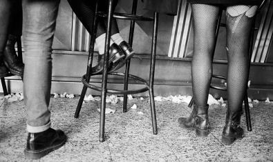 Una de las fotografías de la exposición muestra unos pies calzados con botas punk o skin en la barra de un bar