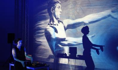 Un moment de l'espectacle amb una noia ballant i una altra fent projeccions sobre el mur