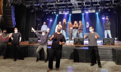 Los once integrantes de la formación con mascarillas y haciendo el signo de la victoria con los dedos de la mano durante la grabación de una canción