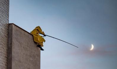 L'artista retratat d'esquenes dalt d'un edifici sostenint una canya de pescar amb la lluna al fons