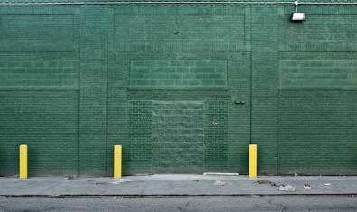 Una de les façanes retratades per l'artista mostra una façana amb les parets i finestres tapiades i pintada de color verd