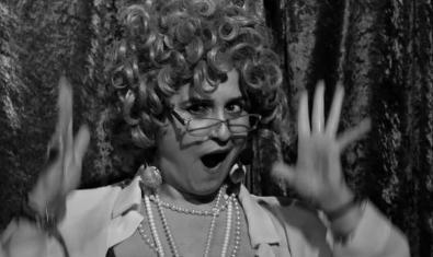 Retrat d'escena de l'artista que fa de mestra de cerimònies del cabaret amb ulleres i les mans aixecades mirant a càmera