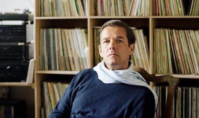 El músic alemany retratat amb una bufanda blanca a l'interior d'un estudi amb una prestatgeria plena de vinils al darrere