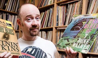 El DJ retratat davant uns prestatges plens de discos i amb dos vinils a les mans