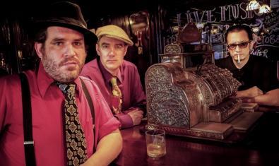 Els tres membres de la banda retratats al costat de la caixa registradora modernista d'El Paraigua