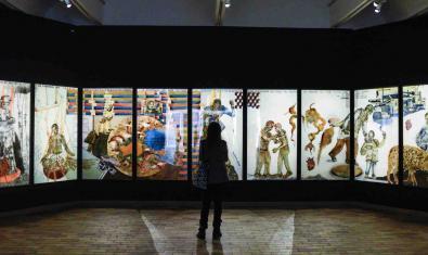 Una visitant davant d'un seguit de quadres de colors vius il·luminats en una habitació a les fosques