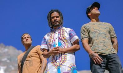 Los tres miembros de la banda vestidos con camisas de colores vivos y retratados contra un cielo de un azul intenso