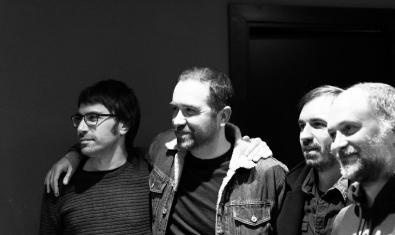 Els quatre integrants de la banda retratats agafats per les espatlles en blanc i negre