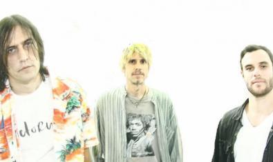 Els tres integrants de l'actual formació de la banda retratats contra un fons blanc