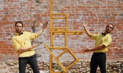 Los dos actores apilando sillas