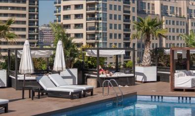 Vista de la piscina d'hotel on es fa l'activitat amb els edificis de Diagonal Mar de fons