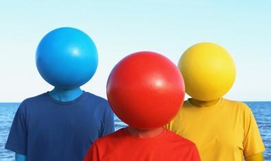 Els tres integrants de la banda retratats davant del mar amb tres pilotes de platja de colors vius col·locades al cap
