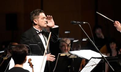 Santiago Auserón en mig de l'orquestra, en concert.