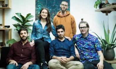 Los cinco componentes del grupo en el sofá, mirando a cámara.