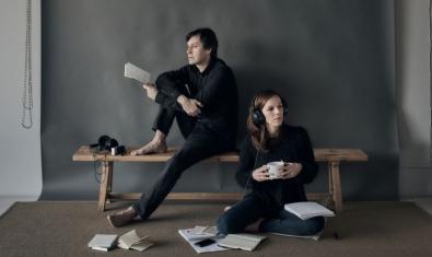 Un actor y una actriz de la compañía con un libro en la mano y con auriculares para escuchar música puestos