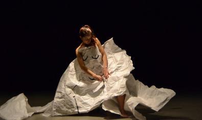 La artista sentada en una silla y vestida con un traje de papel
