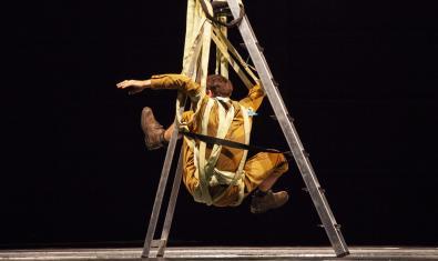 Un artista hace equilibrios dentro de una escalera plegable en un momento de la función