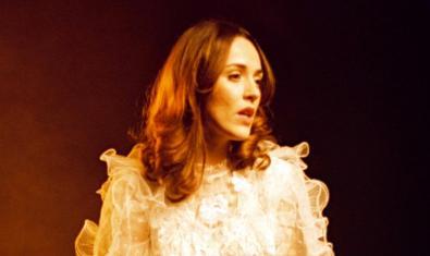 L'artista retratada amb el cabell llarg i amb un vestit blanc de blonda