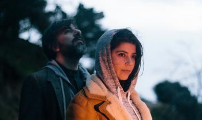Los dos integrantes de la banda retratados en exteriores ella con el cabello cubierto por una capucha