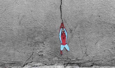 Uno de los grafftiti de este artista francés que aprovecha una grieta para suspender la image de Spiderman