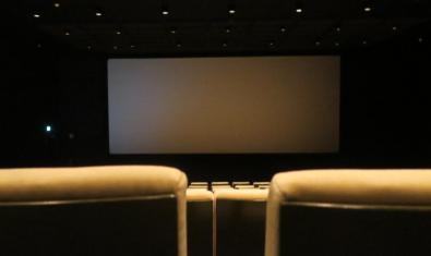 Imagen de una sala de cine vacía con la pantalla a oscuras