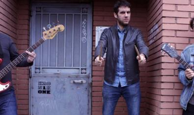 Els tres membres de la banda retratats amb els seus instruments al portal d'una casa