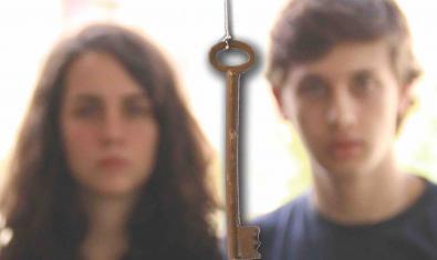 Retrat dels joves protagonistes desenfocats i amb una clau en primer pla entre tots dos